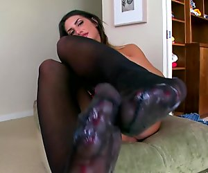 Busty babe wanking a big cock with her feet