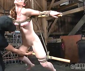 Fixed with ropes to two wooden sticks submissive chick gets mouthfucked